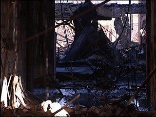 School fire still smolders, demolition needed