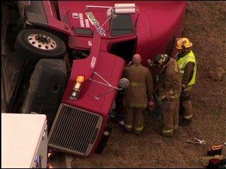 Tractor-trailer truck rolls over, blocks traffic